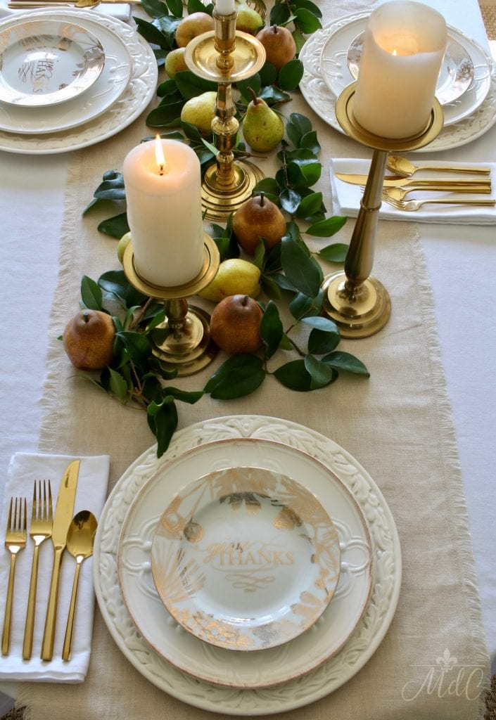 thanksgiving table with white dishes gold flatware and brass candleholders