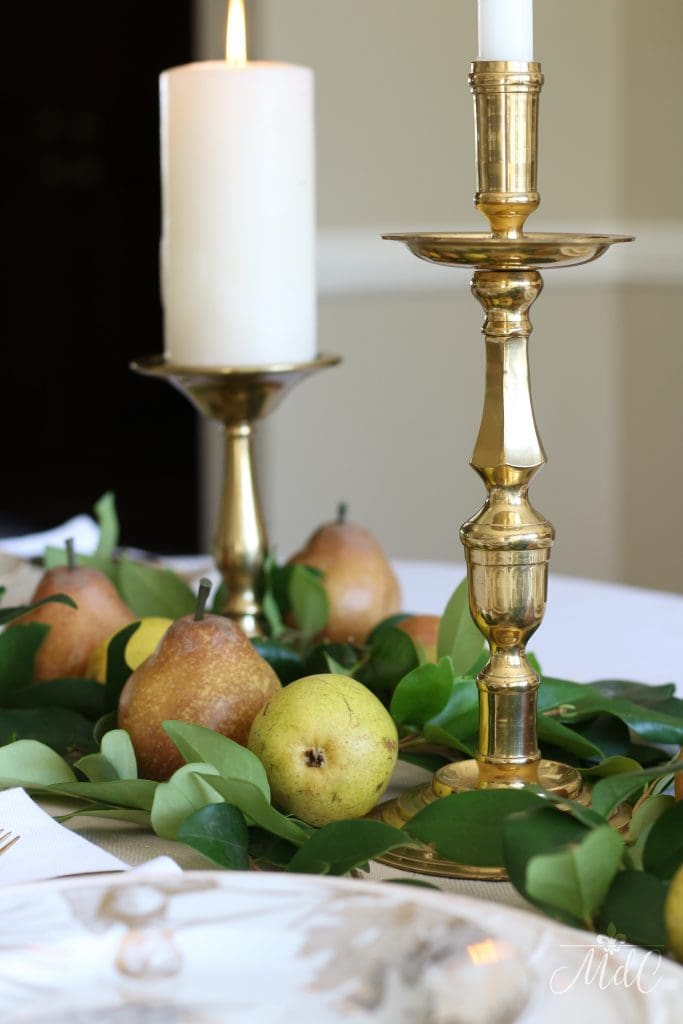 thanksgiving table with gold and green pears and brass candleholders 2