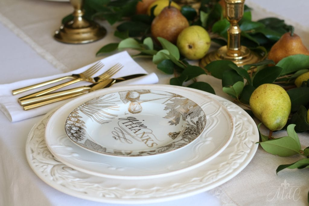thanksgiving table with give thanks plates in gold and white