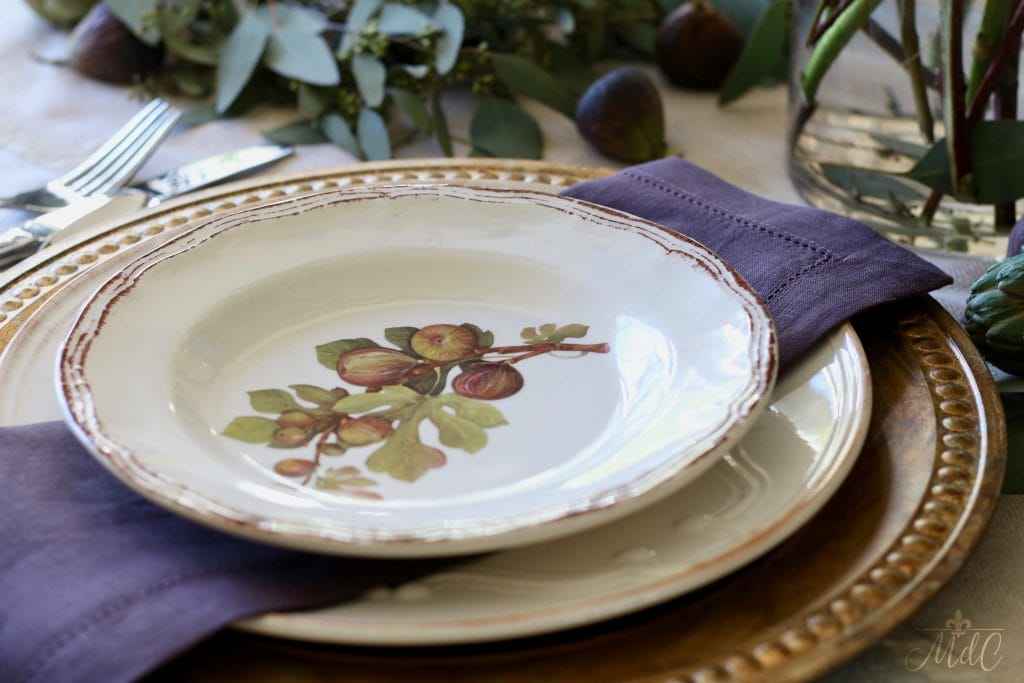 thanksgiving table figs plates over gold chargers with deep purple napkins
