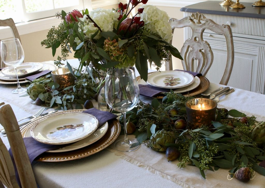 thanksgiving table with runner of eucalyptus figs and artichokes rich fall colors