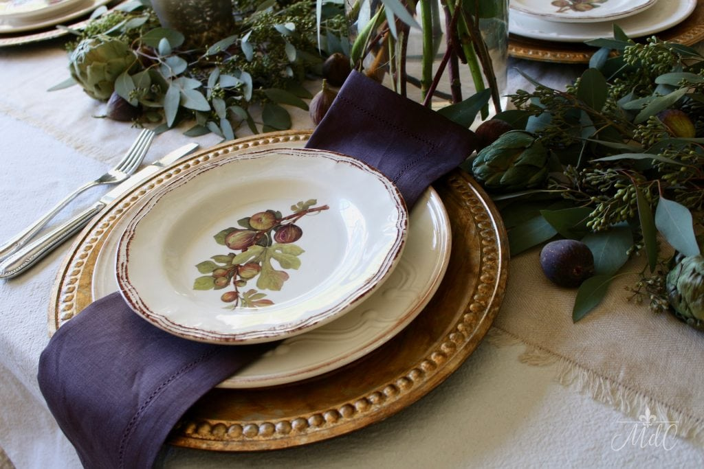 thanksgiving table fig plates and gold chargers with deep plum napkins and eucalyptus
