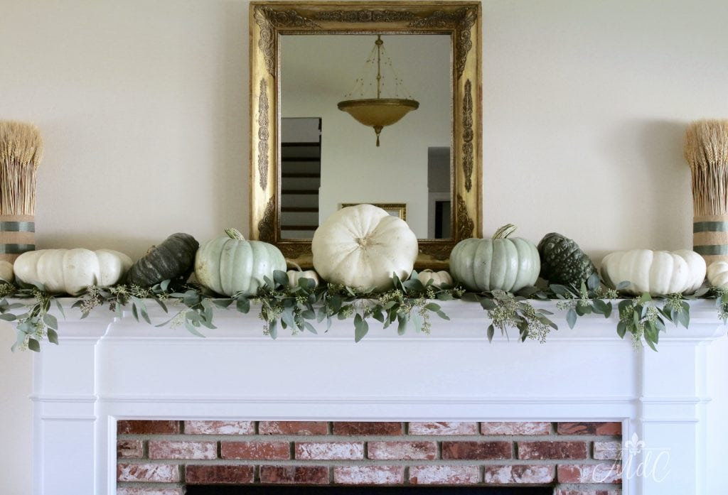 neutral fall mantel with wheat bundles white and green pumpkins and eucalyptus