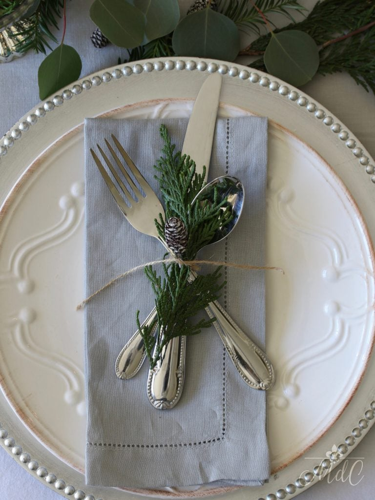 christmas tablescape table setting grey napkin silver charger white plate pinecone greens