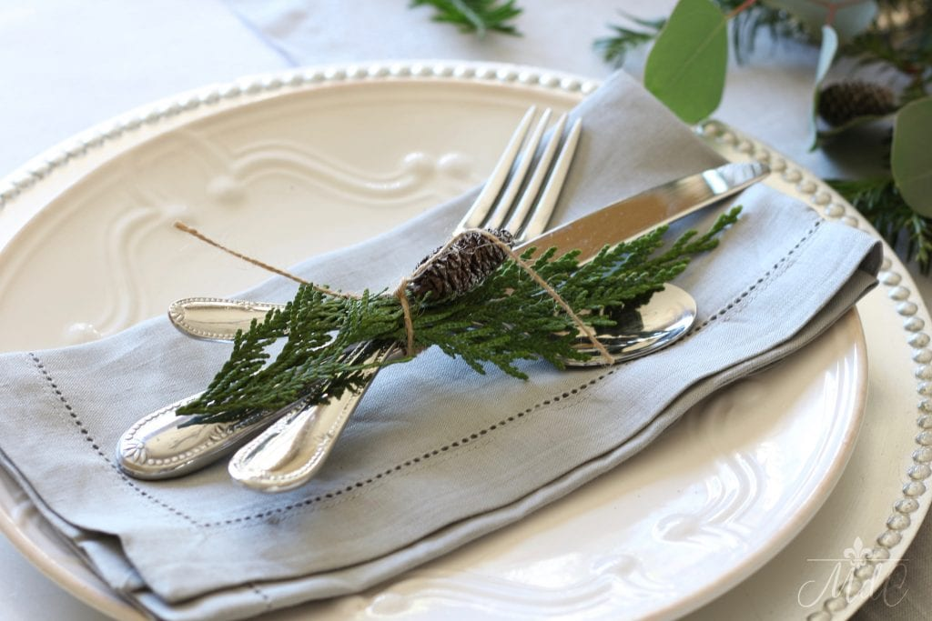 christmas tablescape grey linen napkins flatware greens pinecones