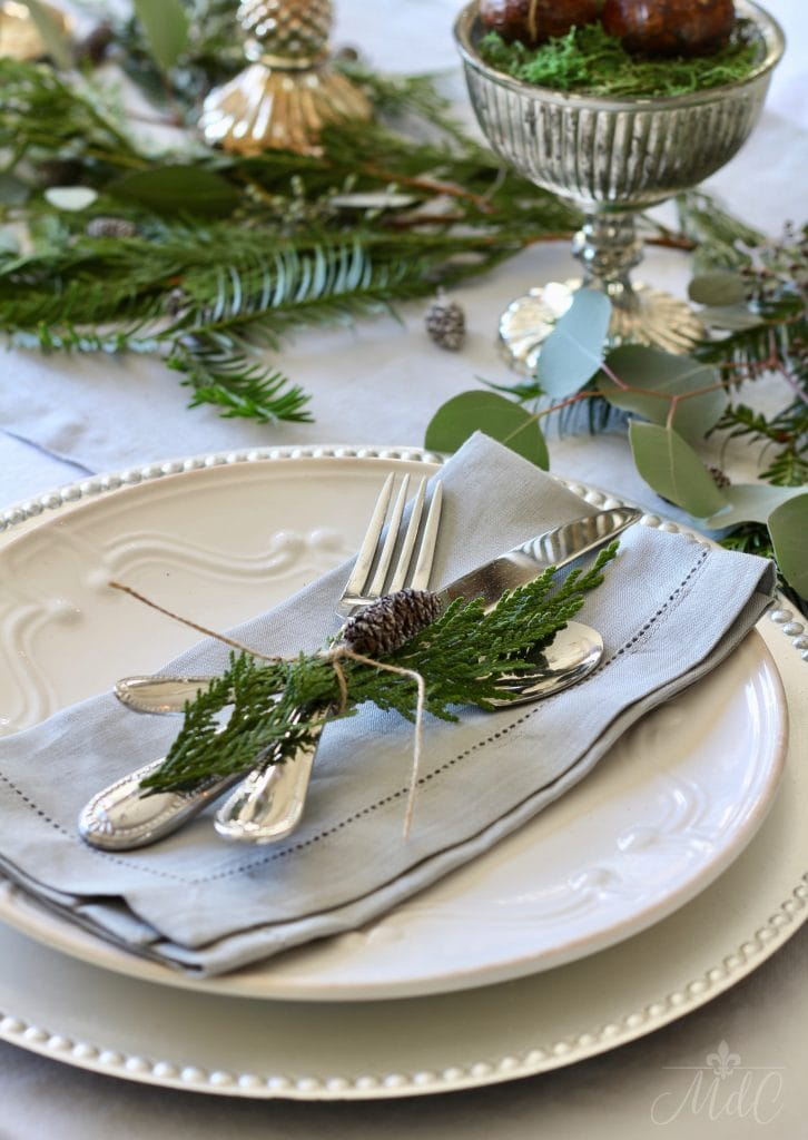 christmas tablescape white plate silver charger greens pinecones mercury glass container holiday table