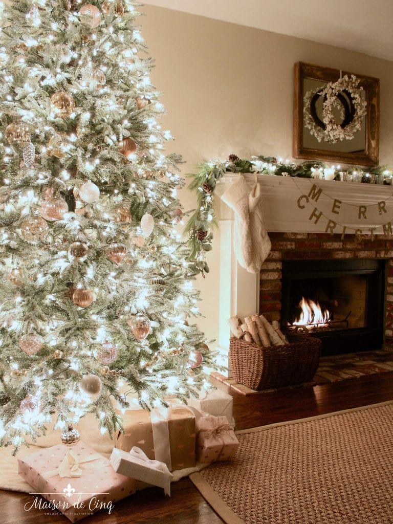 Christmas nights tour tree lit up by fireplace mantel with garland stockings and wreath