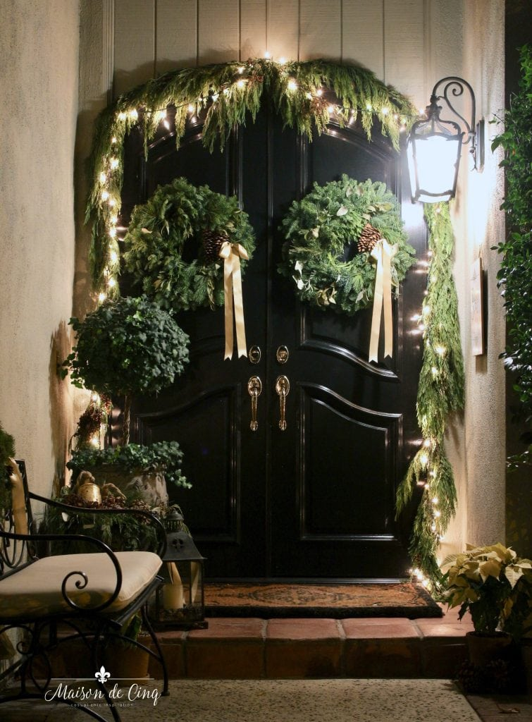 Christmas nights tour black front door with wreaths and garland