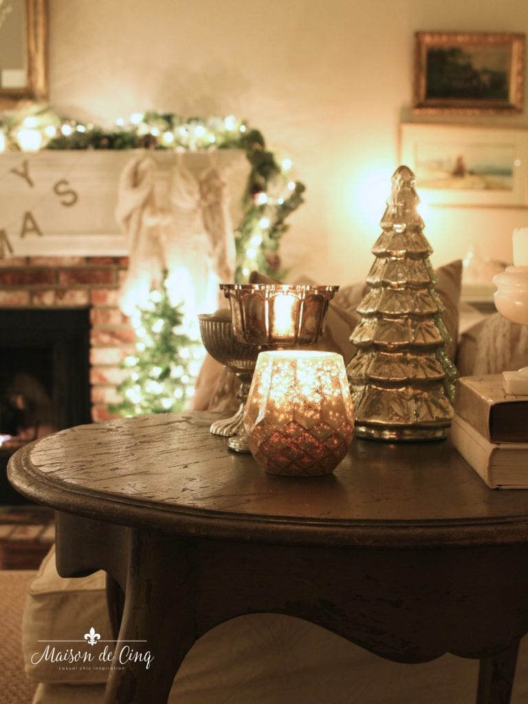 Christmas nights tour candle and mercury glass tree on table with lit Christmas tree behind beautiful holiday decor