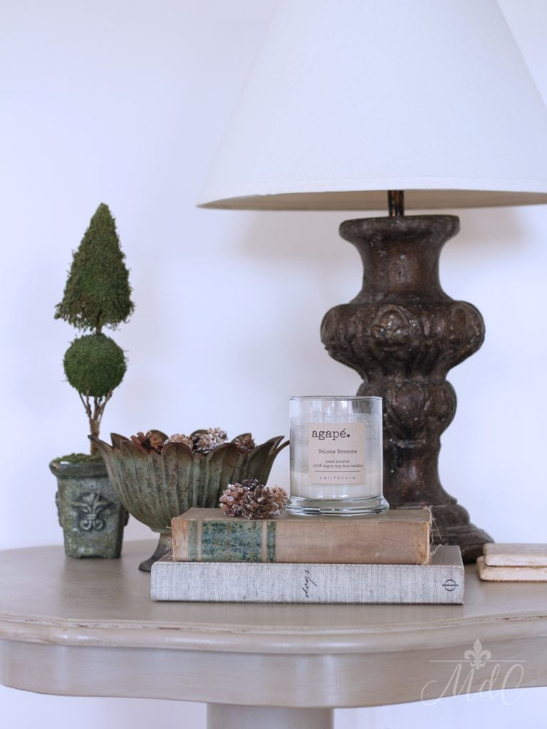 winter decorating ideas greens pine cones books vignette lamp table