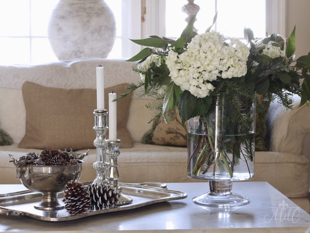 winter decorating ideas styling coffee table greens flowers pine cones silver accessories