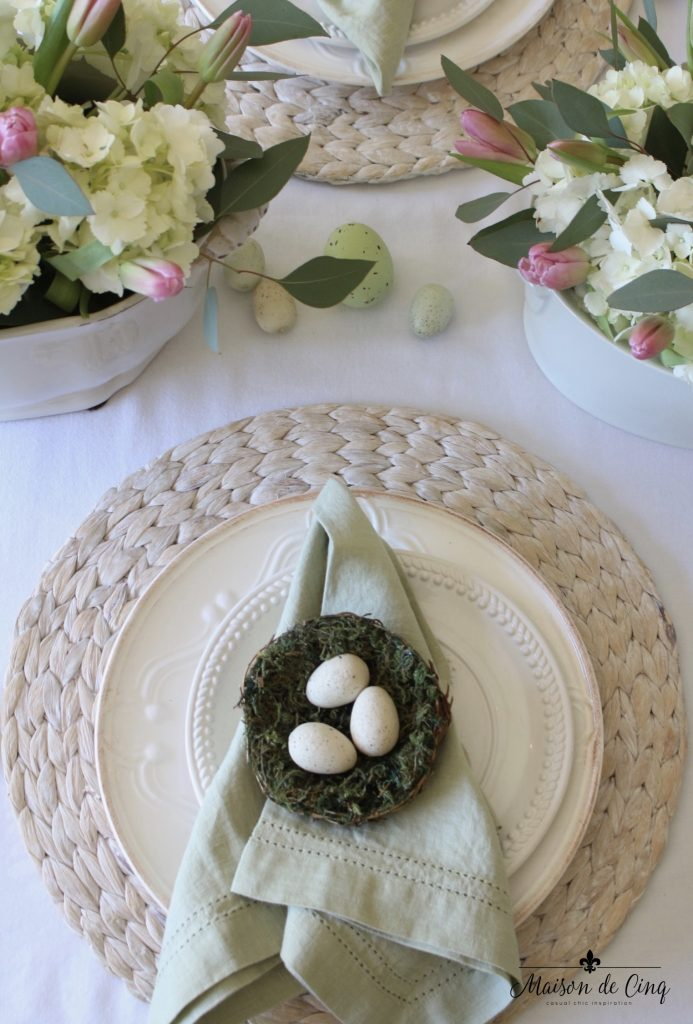 easter tablescape white plates nest eggs green napkins pink and white flowers spring table