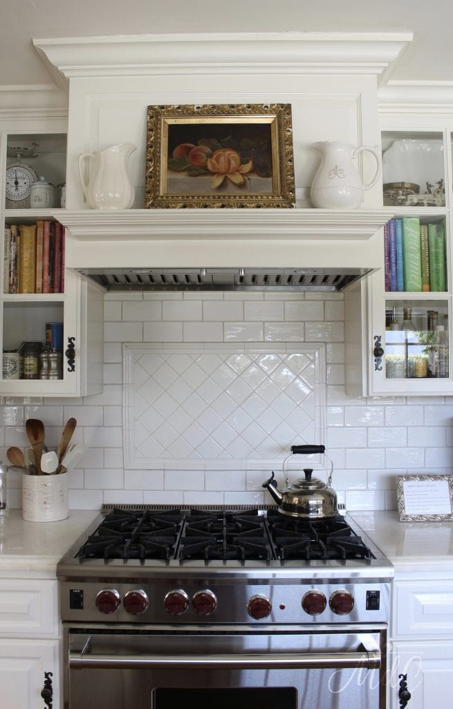 artwork in gorgeous white farmhouse kitchen oil painting over range mantel