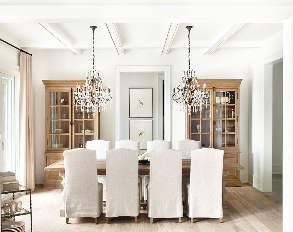 restoration hardware table white slipcovered chairs two china cabinets chandeliers gorgeous dining room