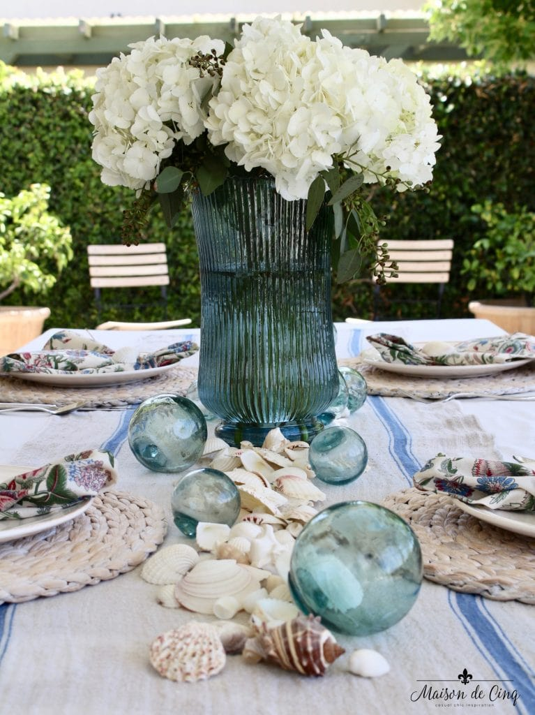 coastal tablescape with white hydrangeas fishing floats and shells