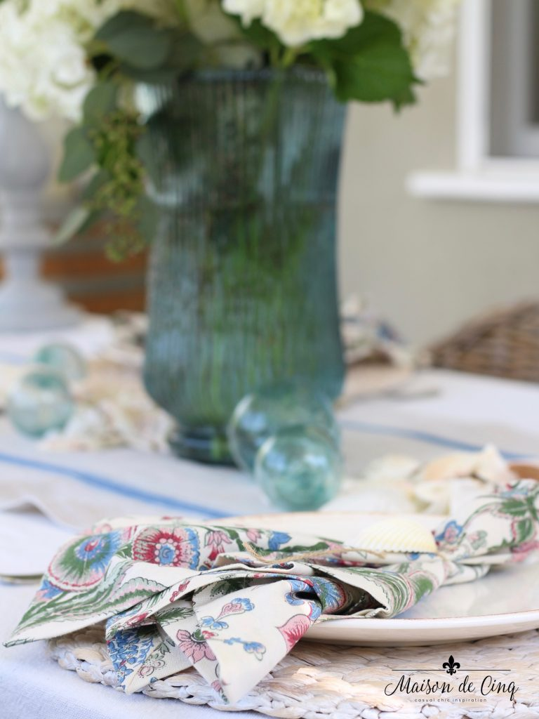 coastal tablescape floral napkins shells blue vase summer table setting