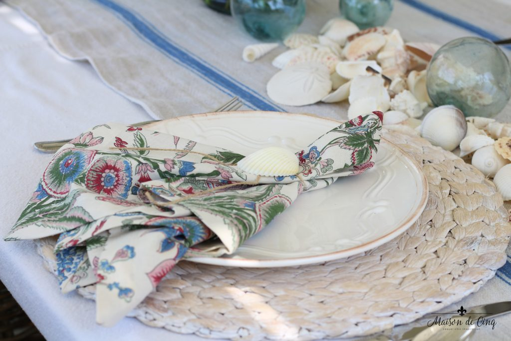 coastal tablescape willow charger white plate floral napkin shells blue striped runner