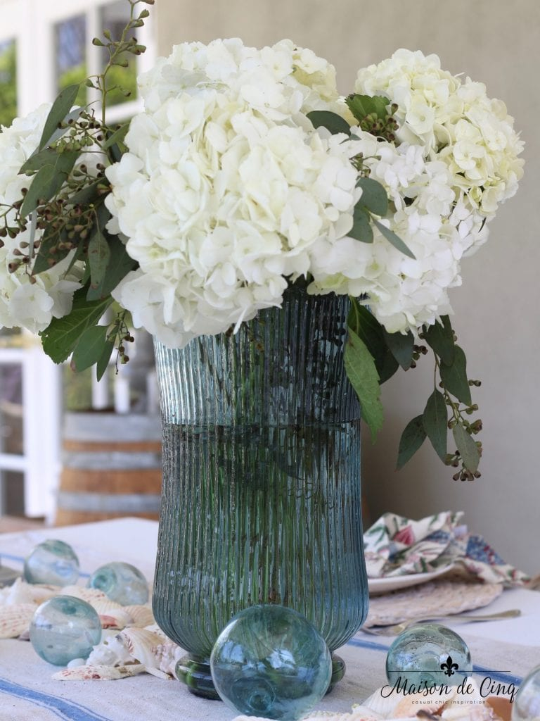 coastal tablescape white hydrangeas blue vase fishing floats blue striped runner summer table