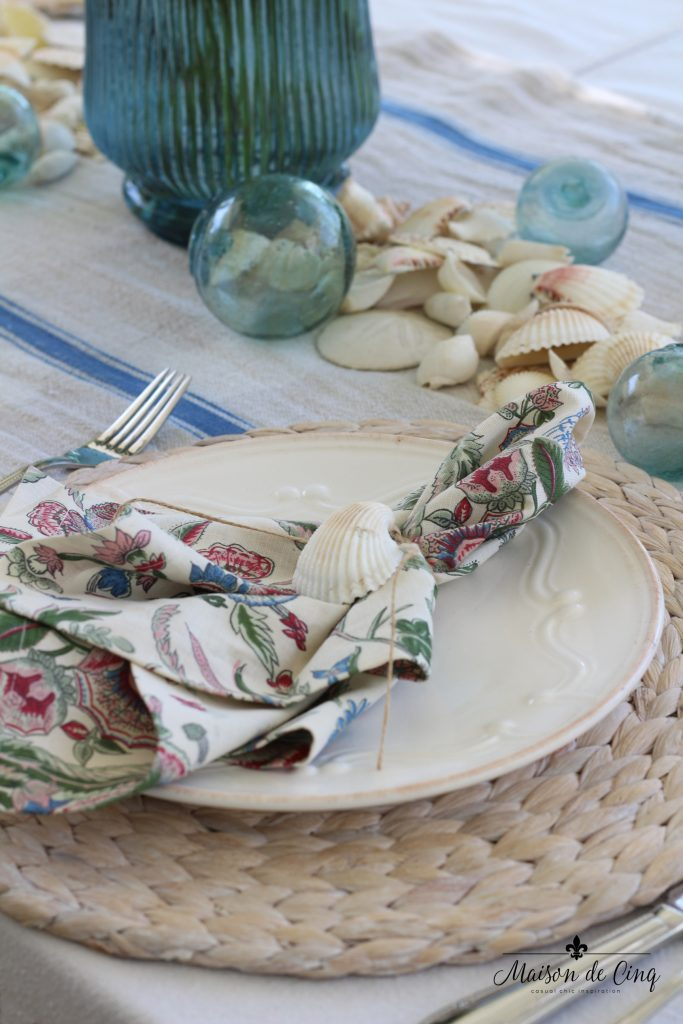 coastal tablescape printed napkin shells fishing floats natural willow charger