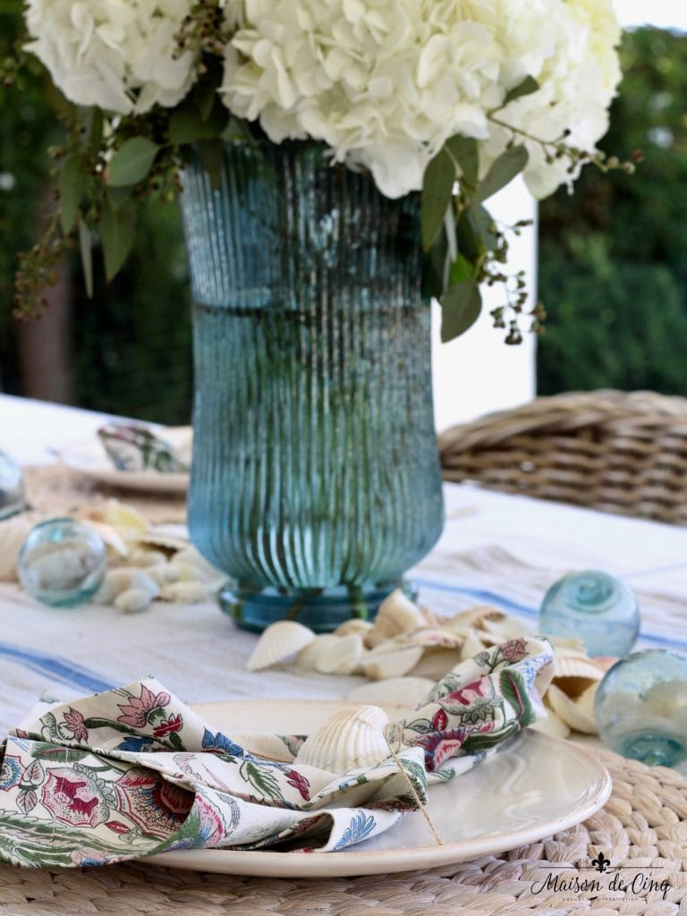 coastal tablescape blue vase white hydrangeas shells fishing floats wicker chairs perfect summer table