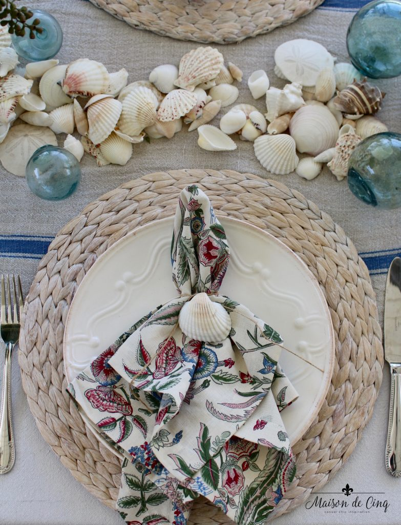 coastal tablescape willow charger white plate floral napkin shells fishing floats summer table