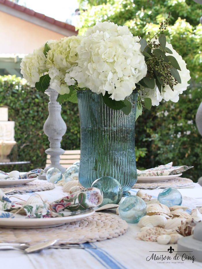 coastal tablescape white hydrangeas blue vase outdoor summer tablesetting