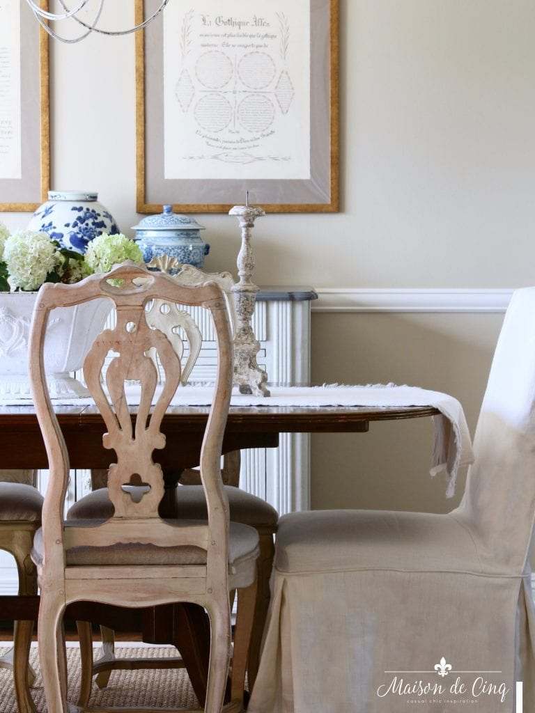 blue and white ginger jars in gorgeous french country dining room slipcovered chairs artwork urn with hydrangeas