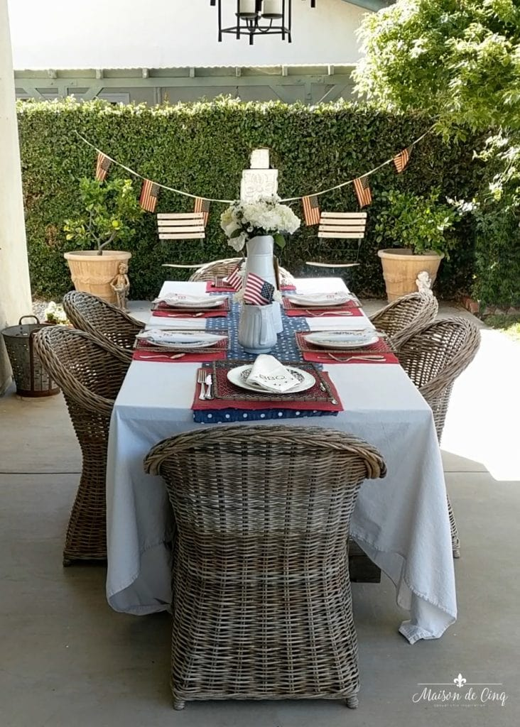 patriotic tablescape in french country style patio garden with wicker chairs and flags
