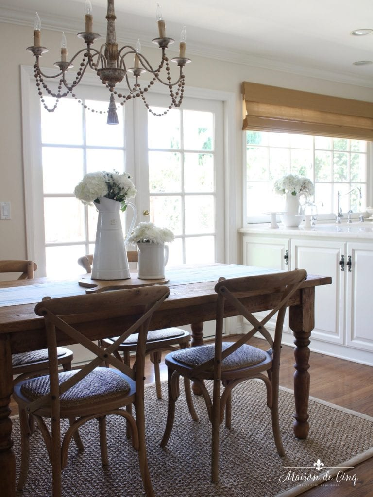 summer kitchen tour breakfast area with pretty chandelier and farmhouse table and chairs white kitchen