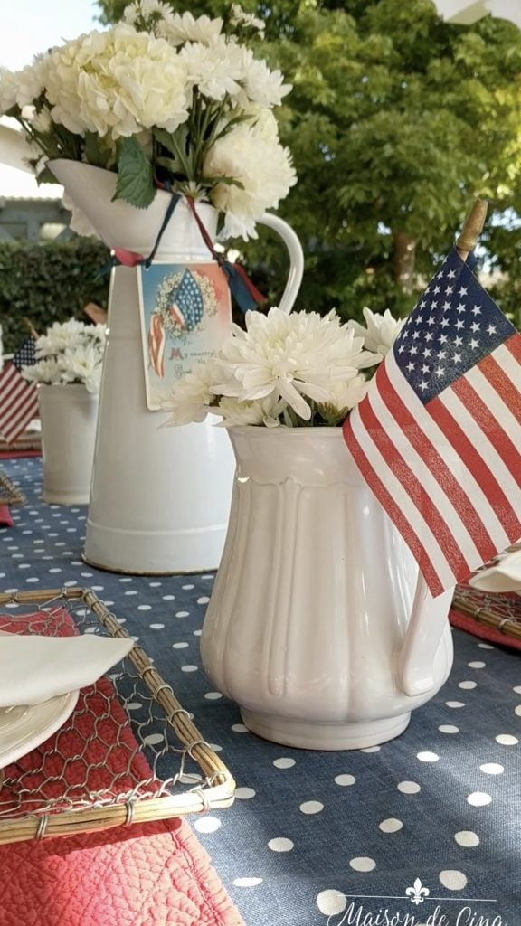 patriotic tablescape red and blue decor flags white flowers in white pitchers