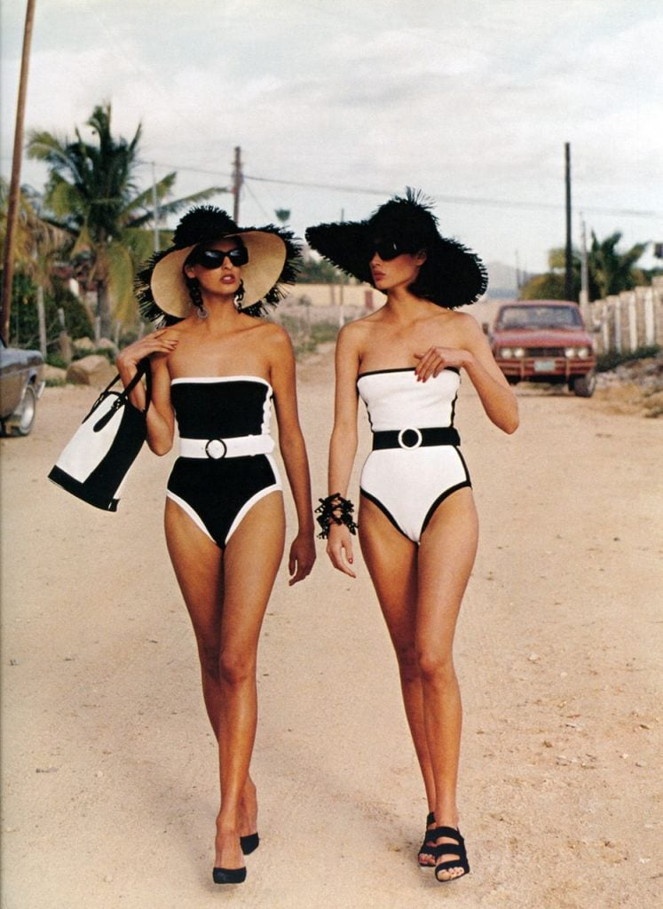 black swimsuit and white swimsuit two classy women strolling in sun hats and heels