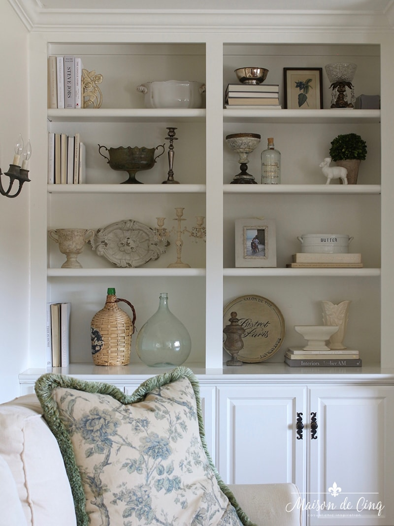 how to style book shelves white cabinets built ins neutral styling decor green floral pillow