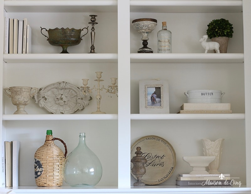 how to style book shelves close up of items on shelf white and cream vases candleholders