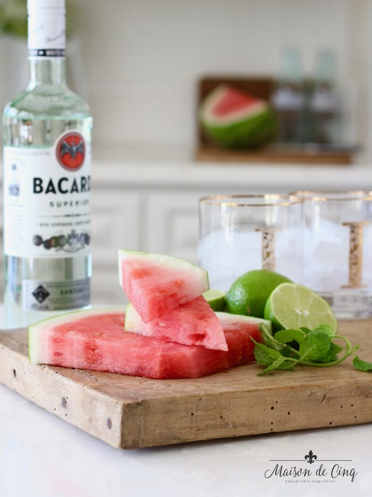 watermelon mojito cocktail with watermelon, rum, mint and limes on cutting board