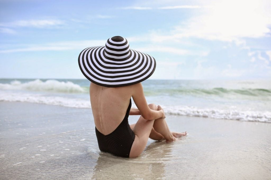 black swimsuit striped hat woman sitting on beach