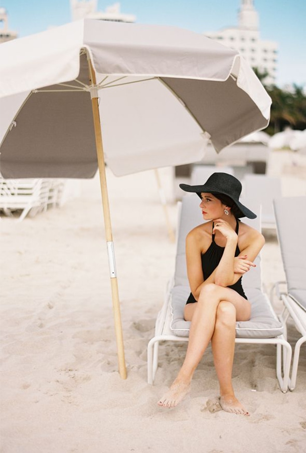 black swimsuit beach umbrella lounge chair sun hat