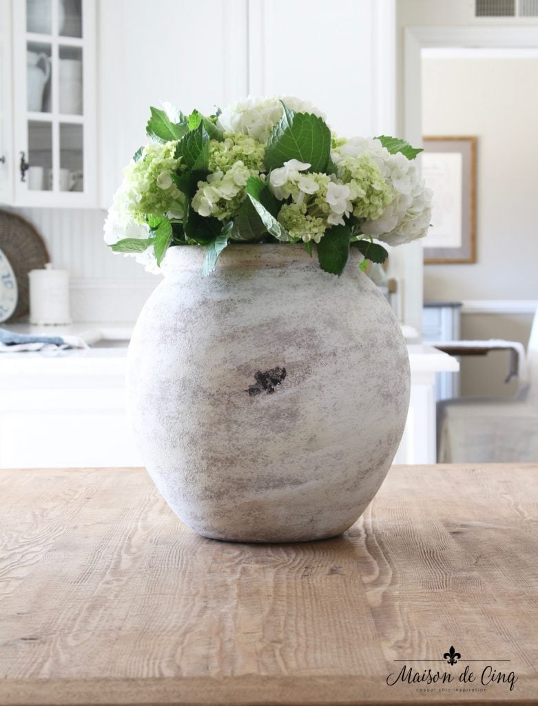 farmhouse table with white vase white and green hydrangeas in white kitchen