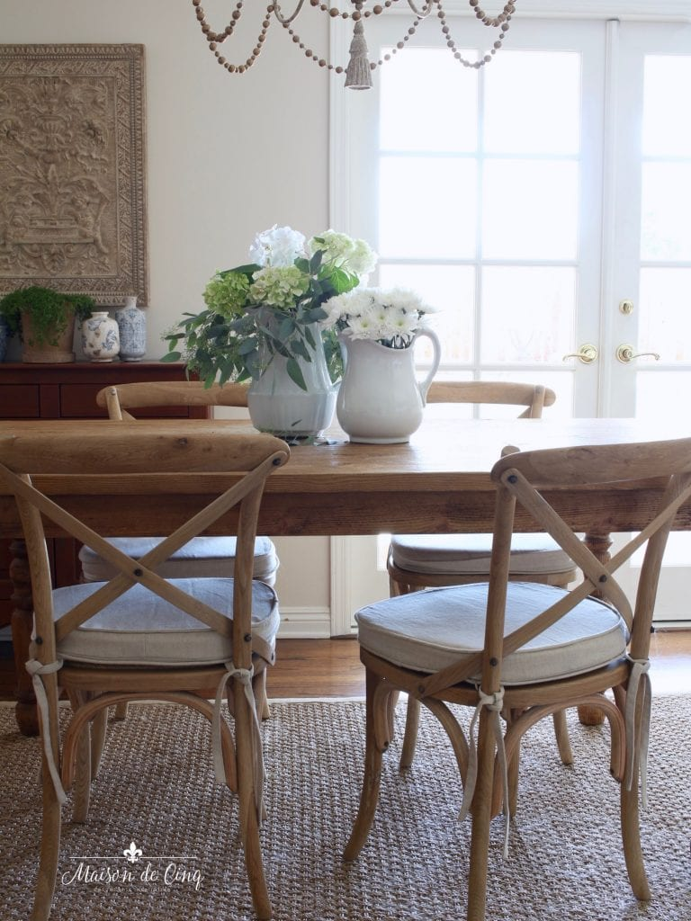 french cafe chairs with cushions farmhouse table flowers chandelier french country