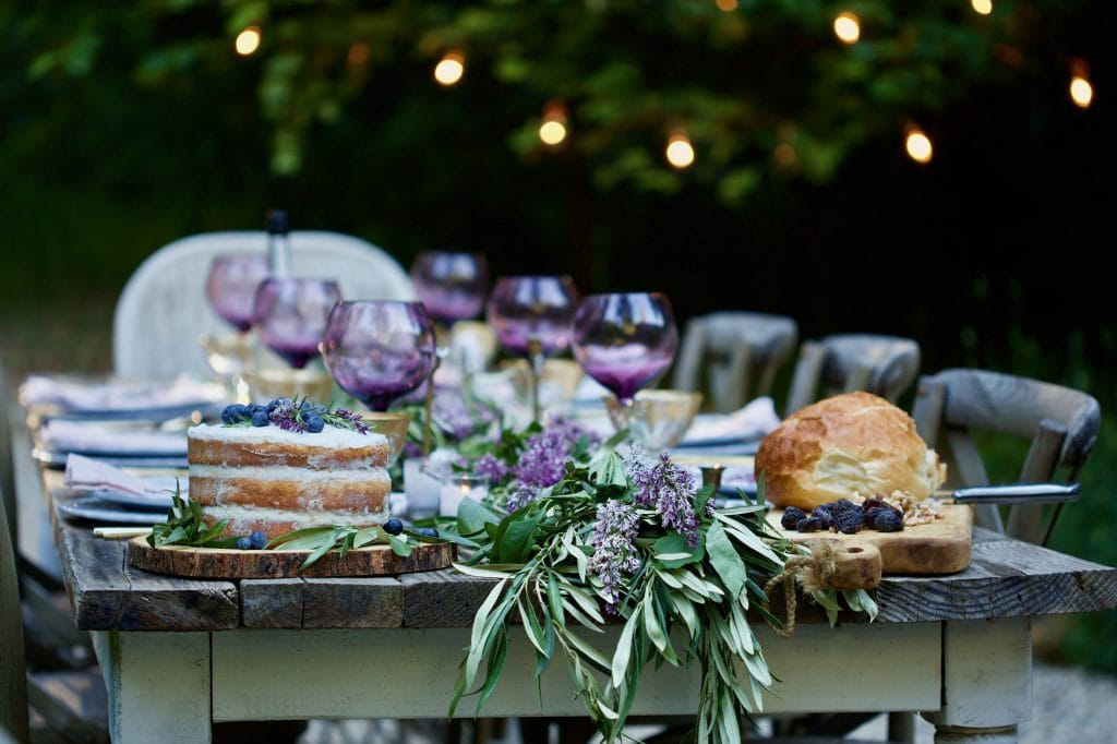 french country cottage beautiful table setting outdoor purple flowers wine glasses food
