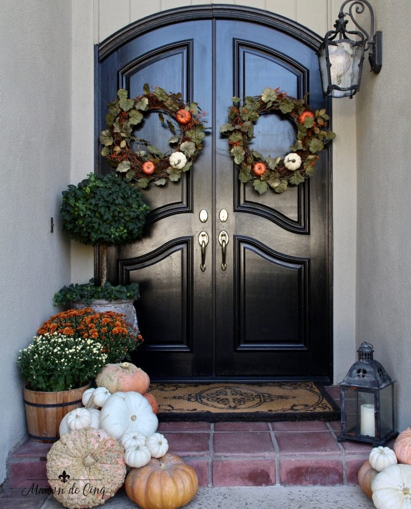 fall front porch warm fall colors wreaths pumpkins mums black doors
