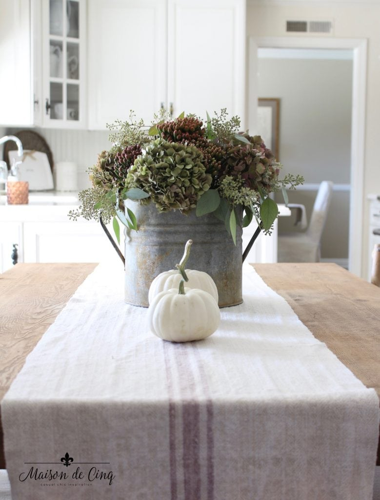 fall kitchen tour hydrangeas with white pumpkins on grain sack runner in white farmhouse kitchen french country