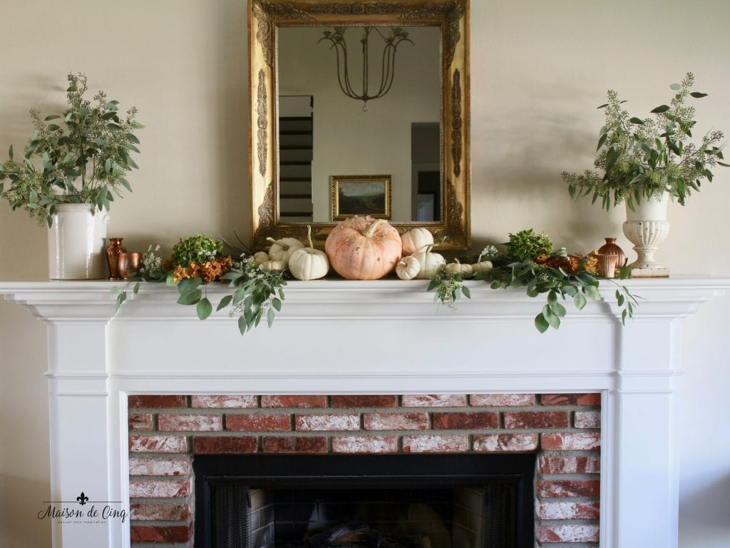 fall mantel brick fireplace gold mirror eucalyptus white and orange pumpkins copper votives