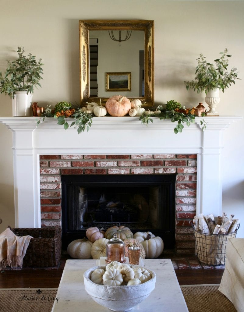 fall mantel pumpkins eucalyptus urns gold mirror brick fireplace
