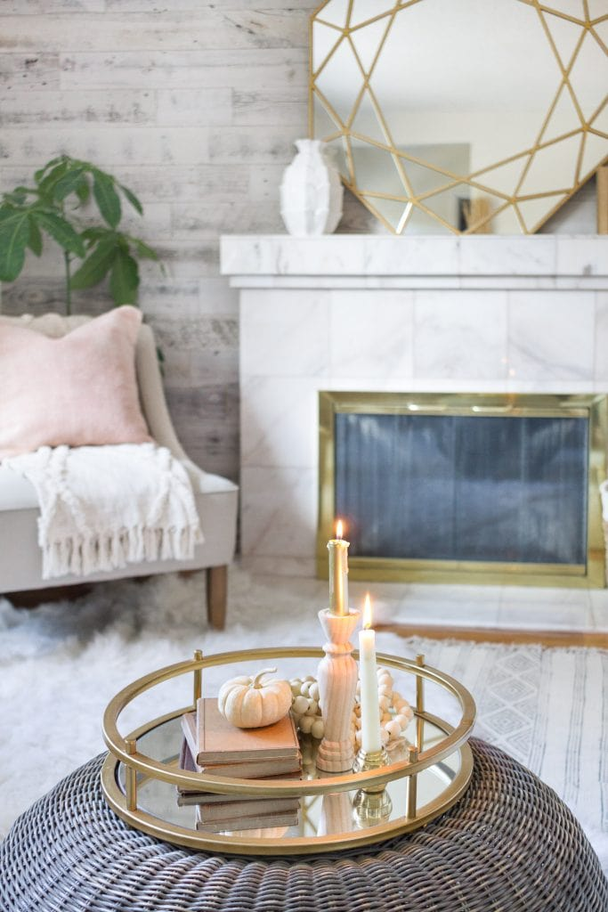 Wicker ottoman with candles on it and a brass tray.
