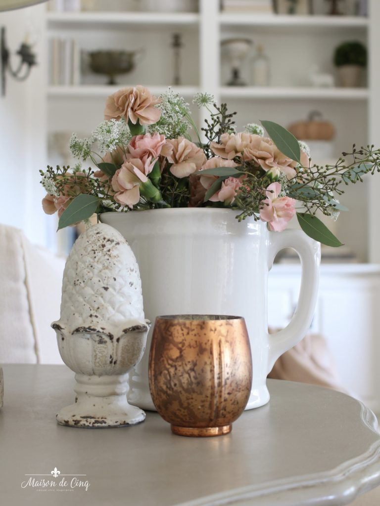 fall family room coral flowers in white pitcher and copper votive fall decor