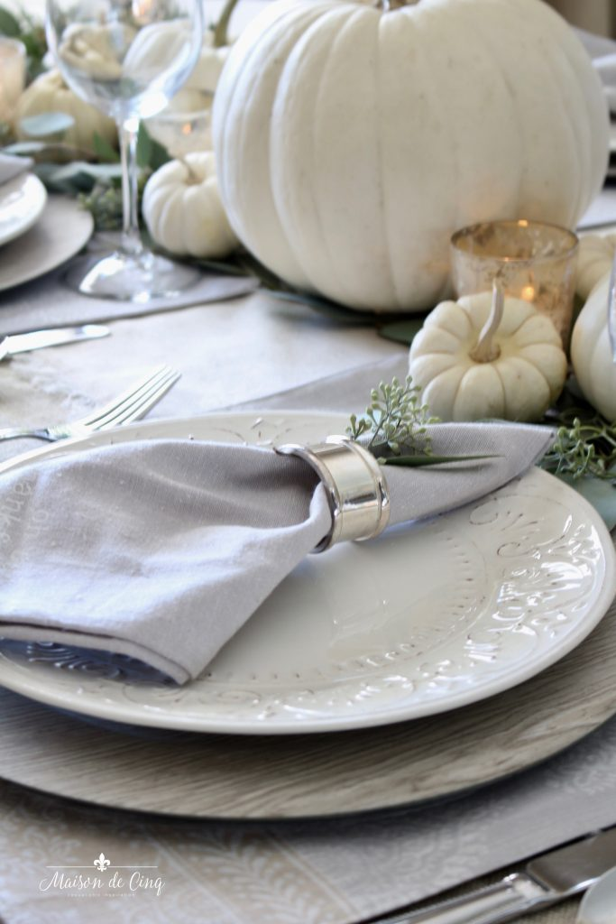 neutral fall table white plates wood grain chargers white pumpkins and greens