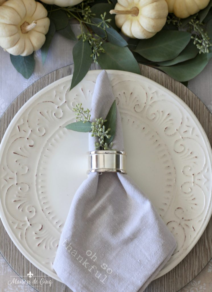 neutral fall table white plates grey napkin silver napkin rings pumpkins and greens