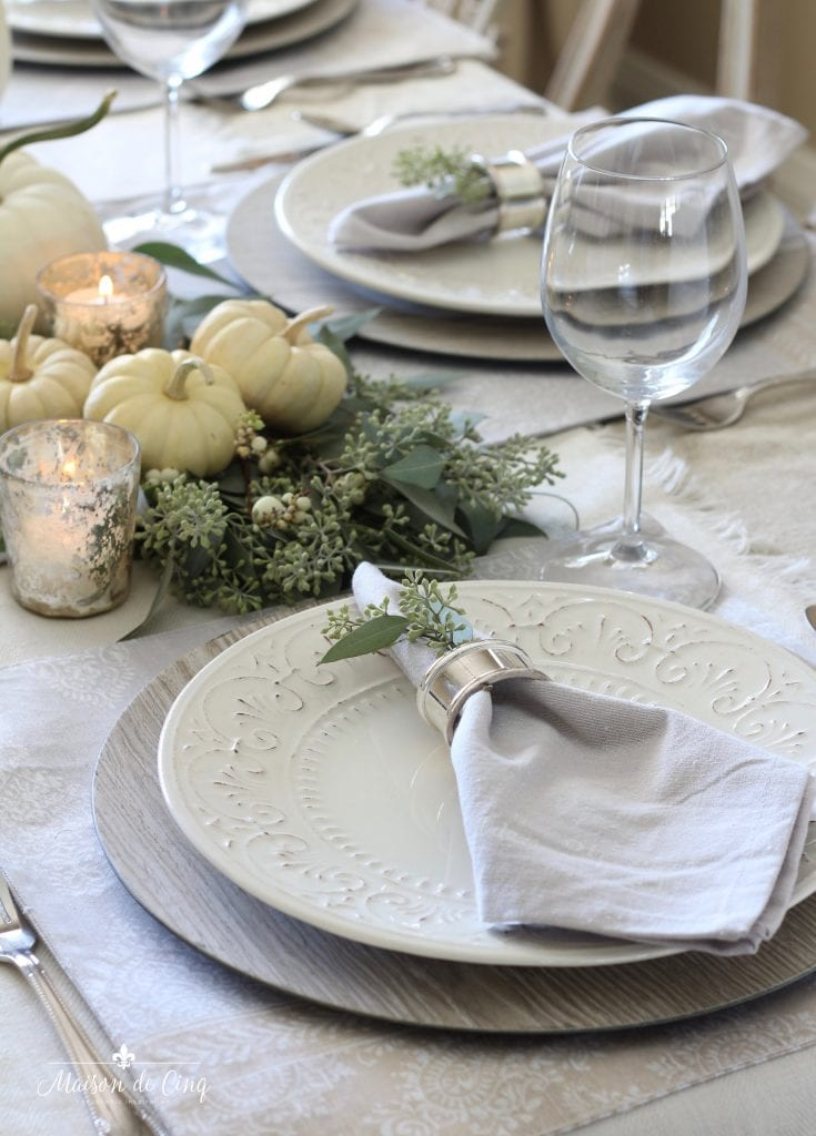 neutral fall table white plates wood grain chargers white pumpkins