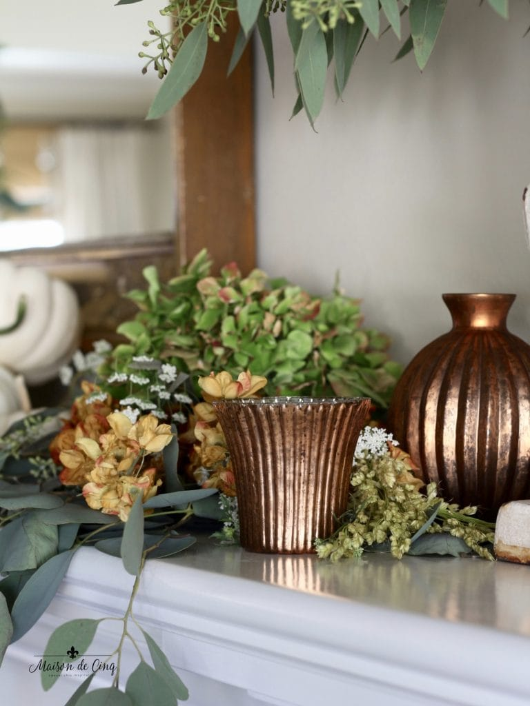 decorating with copper votives on fall mantel with greens and fall flowers