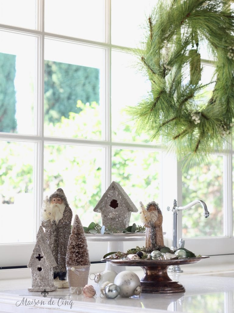 christmas kitchen tour counter vignette with vintage santas houses and bottle brush trees charming holiday decor